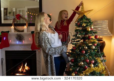 Front view of a happy young Caucasian woman holding her smiling young daughter, decorating the Christmas tree in their sitting room at Christmas time