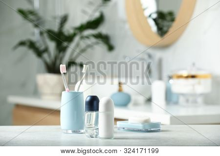 Roll-on deodorants with toiletry on table in bathroom, space for text poster