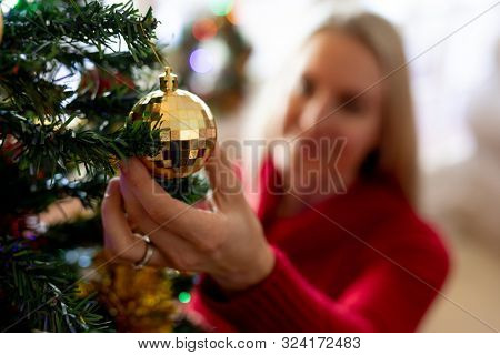 Front view of a smiling young Caucasian woman decorating the Christmas tree in her sitting room at Christmas time