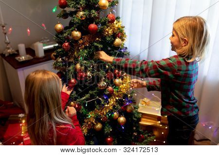 Side view of young Caucasian brother and sister decorating the Christmas tree in their sitting room at Christmas time