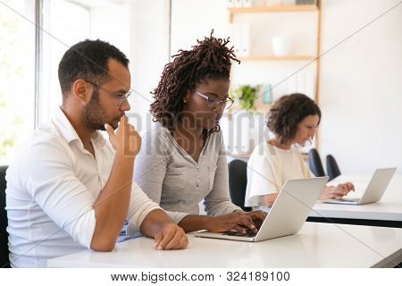 Mentor Watching Intern Working On Computer. Man And Woman In Casual Sitting At Desk In Classroom And