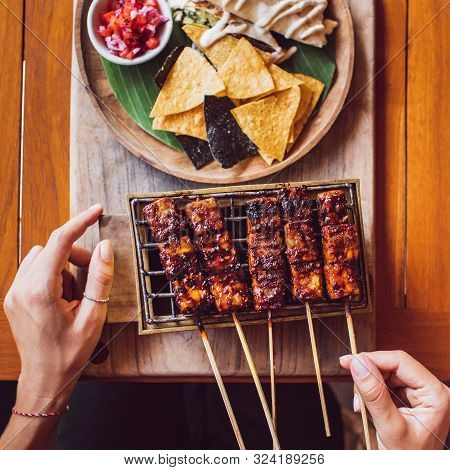 Woman Is Holding Traditional Indonesian Grilled Skewers Of Tempe. Mexican Machos And Guacamole Aside