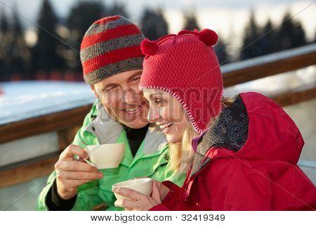 Couple Enjoying Hot Drink In Cafe At Ski Resort