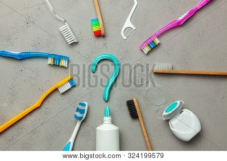 Toothpaste In The Form Of A Question Mark And Many Different And Colored Toothbrushes And Dental Flo