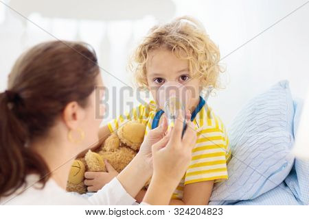 Sick Little Boy With Asthma Medicine. Mother With Ill Child Lying In Bed. Unwell Kid With Chamber In