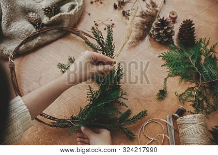 Christmas Wreath Workshop. Hands Holding Herbs, Fir Branches, Pine Cones, Berries, Thread, Scissors