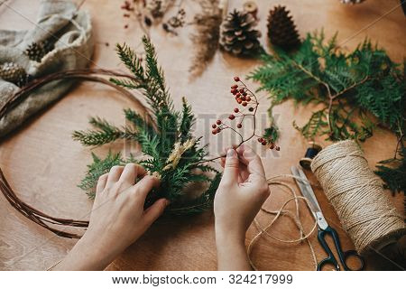 Making Rustic Christmas Wreath. Hands Holding Berries, Fir Branches, Pine Cones, Thread, Scissors On