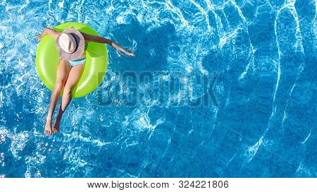 Active Young Girl In Hat In Swimming Pool Aerial Top View From Above, Child Relaxes And Swims On Inf