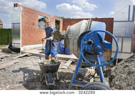 Builder Filling A Conrete Mixer
