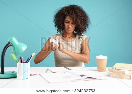 Beautiful upset young african businesswoman casually dressed sitting at the desk isolated over blue background, studying, holding crumpled paperball