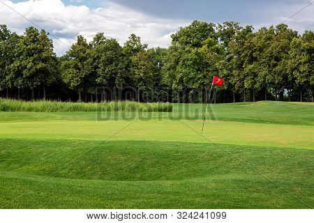 Andscape Of A Golf Course With A Green Lawn And A Hilly Surface Of The Playing Space With A Hole Mar