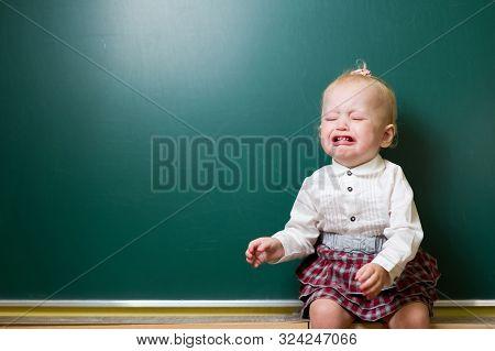Lbaby Girl Crying Near A School Blackboard. Crying Baby On Blackboard Background. Learning Difficult