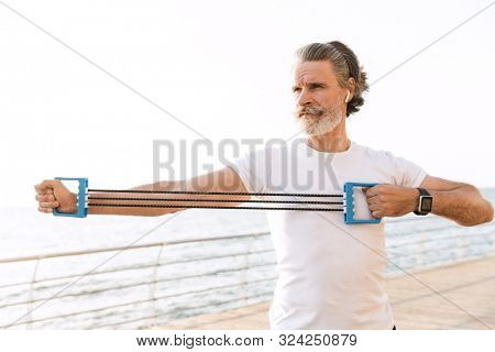 Image of strong mature man in sportswear using earpod while doing exercise with expander near seaside in morning