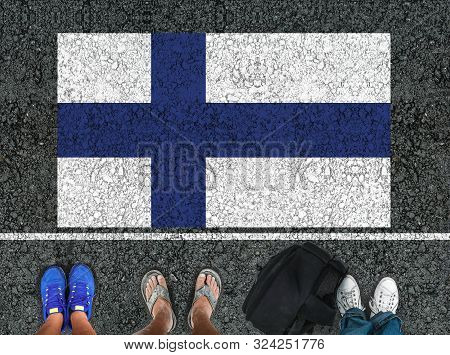 People Legs Are Standing On Asphalt Road Next To Flag Of Finland And Border