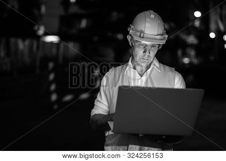 Construction Worker At The Construction Site Using Laptop Computer