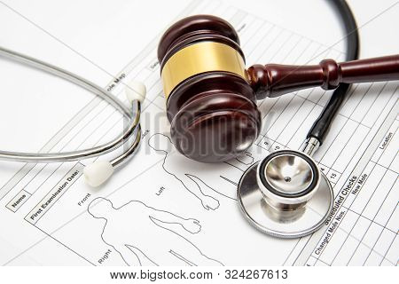 A Wooden Judge Gavel And Stethoscope On A Medical Chart. Medical Dispute Concept.