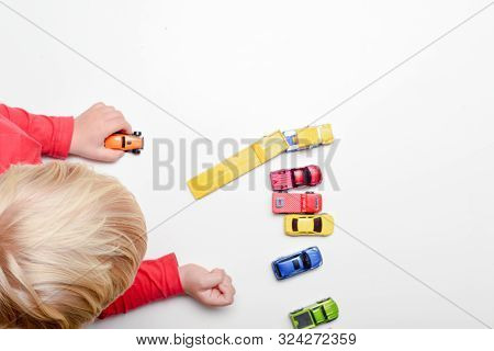 High Angle Shot Of Young Blond Child Playing Alone With Toys