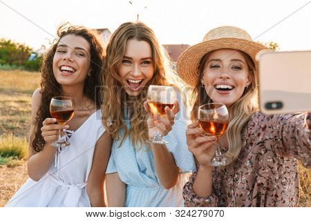 Photo of delighted young women taking selfie photo on cellphone while drinking red wine at countryside during sunny day