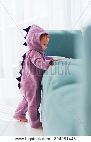Adorable Infant Baby Girl In Cute Dinosaur Costume Is Standing Near The Sofa