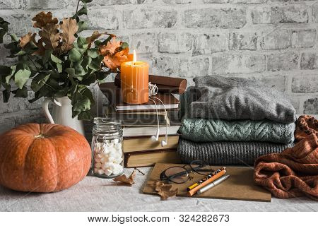 Autumn Cozy Home Still Life. Pumpkin, Stack Of Books, Burning Candle, Pile Of Winter Autumn Sweaters