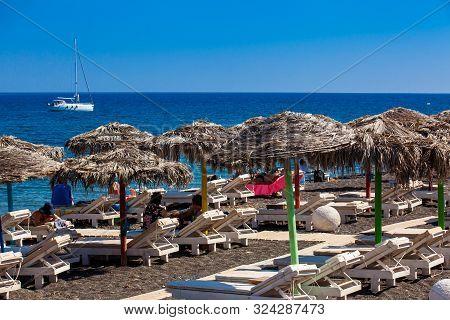 Santorini, Greece - April, 2018: Tourists Sunbathing At The Beautiful Perissa Village Beach In Santo