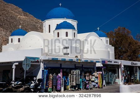 Santorini, Greece - April, 2018: The Stores Next To The Church Of Holy Cross In The Central Square O