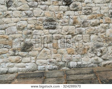 Ancient Stone Wall Paved With Cobblestone With Stone Pavement At An Angle. Stone Wall Building Featu