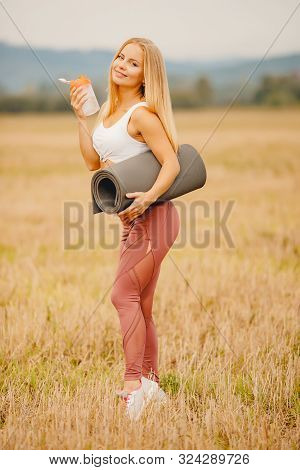 Beautiful blonde girl quenches and drinks thirst with bottle of water, yoga mat, in background park poster