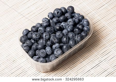 One Portion Blueberry Berry Fruit Is In Plastic Package On Bright Background, Organic Fruit Concept.