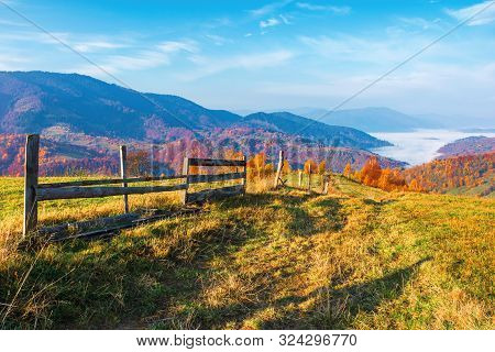 Rural Area In Mountain At Sunrise. Wonderful Golden Autumn Weather With High Clouds On The Blue Sky.