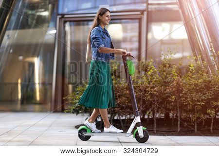 Female commuter riding electric push scooter