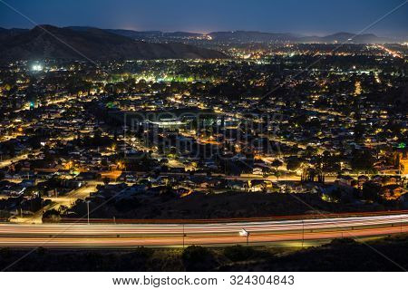 Predawn night view of Simi Valley commuter freeway traffic and suburban homes near Los Angeles in Ventura County, California.