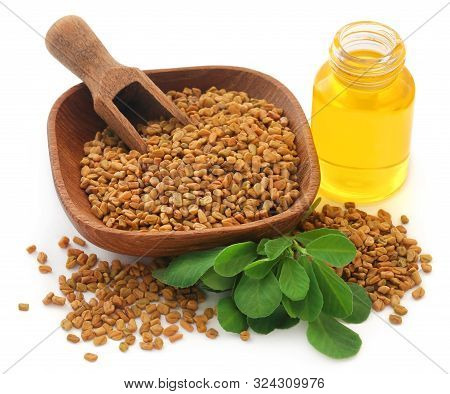 Fenugreek Seeds With Oil In Bottle Over White Background