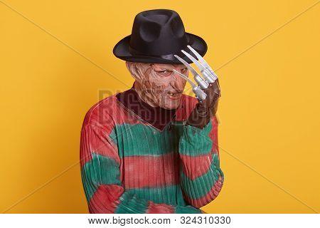 Studio Portrait Of Man In Monster Makeup, Having Long Hose And Ugly Face, Freak Hiding Behind His Ha