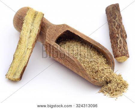 Liquorice Stick And Ground In A Wooden Scoop Over White Ackground