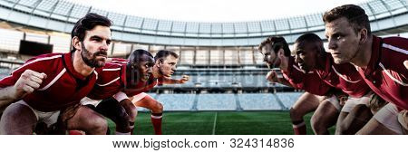 Diverse rugby players on field against rugby stadium at dawn