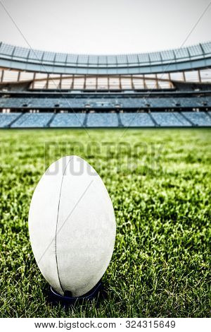 Rugby ball on the pitch against rugby stadium at dawn