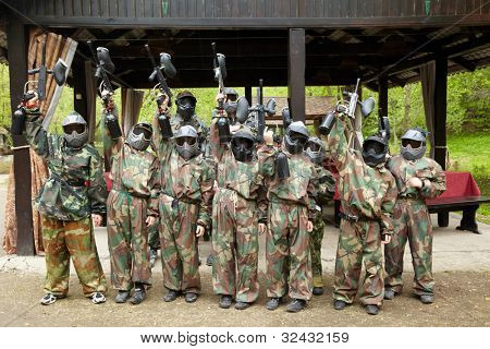 Boys dressed in camouflage stand in a row on a paintball base, raising his paintball gun up.