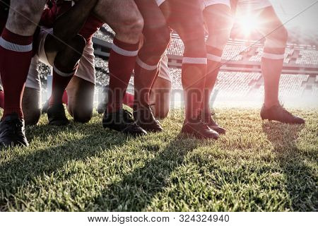 Male rugby players playing rugby in the ground against rugby pitch
