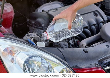 Man Pouring Distilled Water Ecological Alternative To Washing Fluid To Washer Tank In Car, Detail On