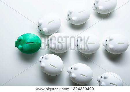 White Piggybanks Following Green Piggybank On White Background