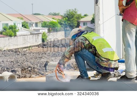 Welder man welding steel bars the supporting the precast concrete wall, worker with unprotected and unsafety. poster