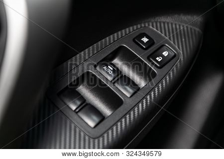 poster of Close up of a door control panel in a new modern car. Arm rest with window control panel, door lock button, and mirror control.