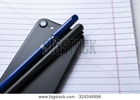 Modern Mobile Phone With Pens On Notebook Close Up Clean Bright Stock Photo Flatlay Product Shot