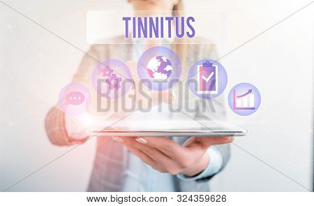 Conceptual hand writing showing Tinnitus. Business photo showcasing A ringing or music and similar sensation of sound in ears Female human wear formal work suit presenting smart device. poster