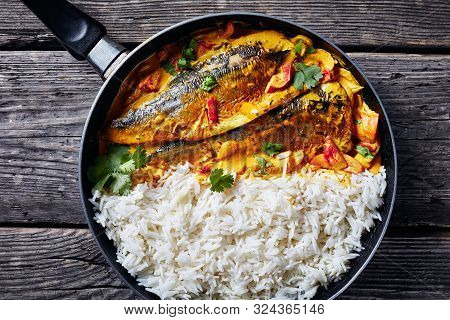 Close-up Of Yellow Curry, Panang Curry With Grilled Saba Mackerel Fish Served With Steamed Long Grai