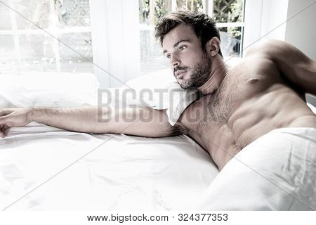 Sexy, Hairy Naked Muscular Man With Sixpack Abs Lying In Bed Covered With Sheet With Window In Backg