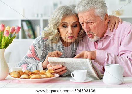Close Up Portrait Of Happy Senior Couple Reading Newspaper