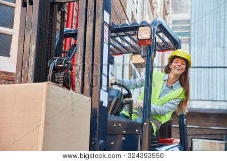 Young woman in logistics. Training to forklift driver on the forklift