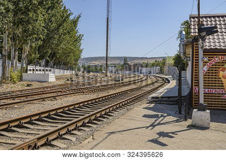 Feodosia, Crimea, Russia - September 11, 2019: Railway Tracks In Feodosia With Mountains In The Back